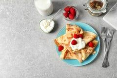 Dünne Pfannkuchen mit Beeren und Creme auf Platte Lizenzfreies Stockfoto