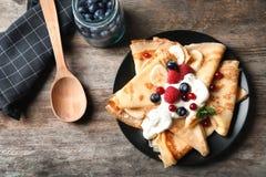 Dünne Pfannkuchen mit Beeren und Creme auf Platte Stockfotografie