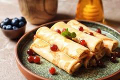 Dünne Pfannkuchen mit Beeren und Honig auf Platte Stockbild