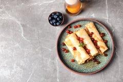 Dünne Pfannkuchen mit Beeren und Honig auf Platte Lizenzfreie Stockfotos