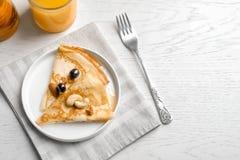 Dünne Pfannkuchen mit Beeren und Nüssen auf Platte Lizenzfreies Stockbild