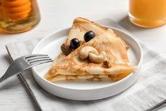 Dünne Pfannkuchen mit Beeren und Nüssen auf Platte Lizenzfreie Stockfotos