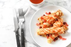 Dünne Pfannkuchen mit Beeren und Sirup auf Platte Stockfotos