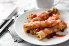 Dünne Pfannkuchen mit Beeren und Sirup auf Platte Stockbilder