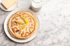 Dünne Pfannkuchen mit Zitrone, Butter und Milch auf Tabelle Stockbild