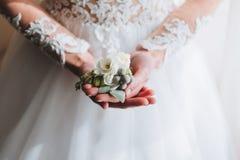 Dünne schöne junge Braut, die einen Boutonniere hält stockbild