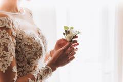 Dünne schöne junge Braut, die einen Boutonniere hält stockbilder