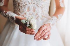 Dünne schöne junge Braut, die einen Boutonniere hält stockfotografie