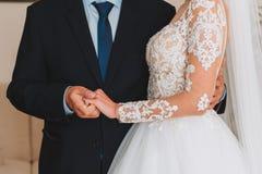 Dünne schöne junge Braut, welche die Hand ihres Vaters vor ihrer Hochzeit hält lizenzfreie stockbilder
