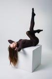 Dünne sexy weibliche lange Beine in der schwarzen Strumpfhose auf Studiokasten Lizenzfreie Stockfotos