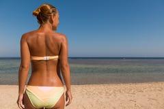 Dünne sinnliche Frau, die das Meer betrachtet Stockfotografie