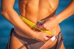 Dünne Sitzfrau im Bikini mit Maßband Lizenzfreies Stockfoto