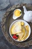 Dünne Sodawasser-Pfannkuchen Blinis mit Zitronenklumpen und Teekanne auf Weinlesebehälter Lizenzfreies Stockfoto