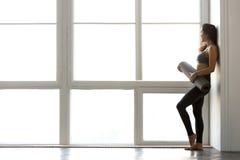 Dünne sportliche attraktive Frau, die Yoga oder Eignung MA halten steht lizenzfreie stockbilder