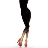 Dünne weibliche Beine in den roten Schuhen Stockfotografie