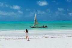 Dünne Yang-Dame auf whitesand Strand, der zum Segel schaut Lizenzfreies Stockfoto