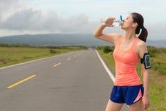 Dünner Frauenläufer, der auf Trinkwasser der Straße steht Stockbilder