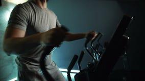 Dünner Körper des jungen männlichen Athleten, der Übung auf Cross-Trainer in der modernen Turnhalle tut, Zeitlupe stock footage