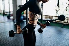 Dünner Körper einer jungen Frau mit Tätowierung in einer schwarzen Sportkleidung, die Muskeln mit Dummköpfen in der Turnhalle auf stockfotografie