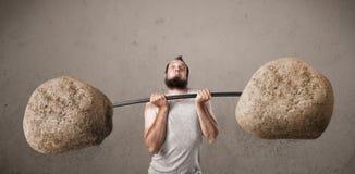 Dünner Kerl, der große Felsensteingewichte anhebt Stockbilder