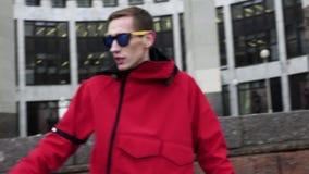 Dünner Mann des Porträts in der roten Jacke und in der Sonnenbrille, die nahe bei Granitsäulen klopft stock video footage