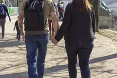 Dünner Mann hält die Hand einer Frau beim Gehen stockbild