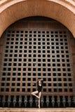 Dünner Tänzer steht auf einem Bein nahe dem alten Tor Stockbilder