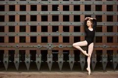 Dünner Tänzer steht auf einem Bein nahe dem alten Tor Stockfotografie