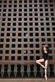 Dünner Tänzer steht auf einem Bein nahe dem alten Tor Stockbild