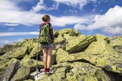 Dünnes athletisches blondes touristisches Wanderermädchen mit Stock und Rucksack c Lizenzfreie Stockfotos