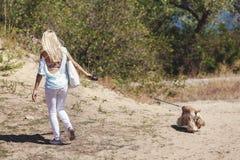 Dünnes blondes Gehen mit einem Hund Stockfoto