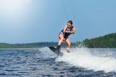 Dünnes Brunettefrauen-Reiten-wakeboard auf Motorbootwelle im See Stockfotografie