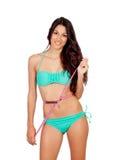 Dünnes Brunettemädchen mit Maßband im Bikini stockfoto