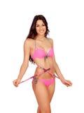 Dünnes Brunettemädchen mit Maßband im Bikini Stockbild