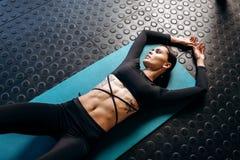 Dünnes dunkelhaariges Mädchen mit der Tätowierung, die in der schwarzen Sportkleidung gekleidet wird, liegt auf der Matte für Eig stockfoto