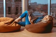 Dünnes junges blondes Lügen auf Couch und Schreiben an ihrem Handy Stockfotos