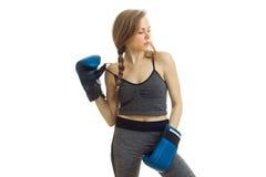 Dünnes junges Mädchen mit Zopf steht in den Boxhandschuhen und blickt in Richtung Stockbild