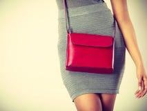 Dünnes Mädchen im grauen Rock mit roter Handtasche Lizenzfreies Stockfoto