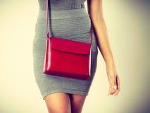 Dünnes Mädchen im grauen Rock mit roter Handtasche Stockfotos