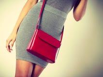 Dünnes Mädchen im grauen Rock mit roter Handtasche Stockbild