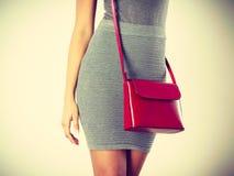 Dünnes Mädchen im grauen Rock mit roter Handtasche Stockfoto