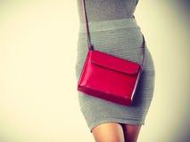 Dünnes Mädchen im grauen Rock mit roter Handtasche Lizenzfreie Stockfotos