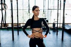 Dünnes schönes Mädchen in der schwarzen Sportkleidung steht in der Turnhalle stockbild