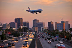 Düsenflugzeug auf der Landungsannäherung, die niedrig über Stadtautobahn fliegt Stockfotos