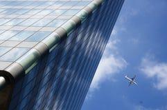 Düsenflugzeug, das niedrig über Handelsbürogebäude fliegt Lizenzfreies Stockfoto