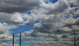 Düsenflugzeug in einem blauen bewölkten Himmel manövriert für die Landung Panoramischer Aufbau lizenzfreies stockfoto