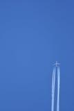 Düsenflugzeug im Flug, die Dampfspuren hinterlassen Lizenzfreie Stockbilder