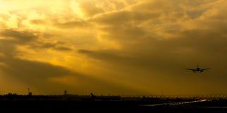 Düstere Flughafenlandschaftslandungsflugzeuge mit der Sonne, die durch Wolken scheint lizenzfreies stockfoto