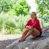 Düstere junge Frau, die auf riesigem Stein für Sommerfrische sitzt Stockfoto