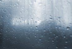 Düstere Landschaft durch das nasse Fenster Lizenzfreie Stockfotos